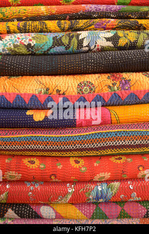 Stack of embroidered and applique textiles from Rajahstan, India - Stock Image