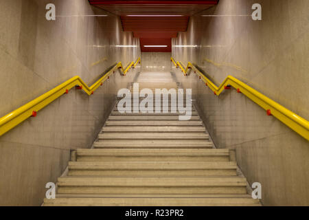 Entrance stairs to the metro of Milan with yellow railing - Stock Image