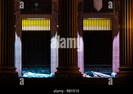 two homeless people sleeping on a library doorway - Stock Image