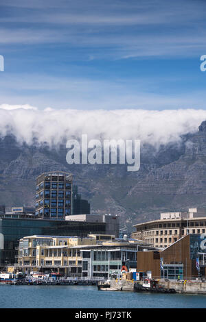 Buildings at the V&A Waterfront in Cape Town, South Africa, with clouds rolling over the top of Table Mountain in the distance - Stock Image