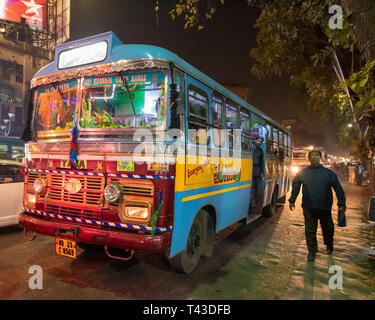 Horizontal view of a public bus driving down the road in Kolkata aka Calcutta, India. - Stock Image