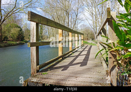 A wooden footbridge over a dyke by the River Bure on a public footpath at Coltishall, Norfolk, England, United Kingdom, Europe. - Stock Image
