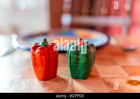 Closeup of colorful bell pepper salt and pepper shakes on table by plate in bokeh background - Stock Image