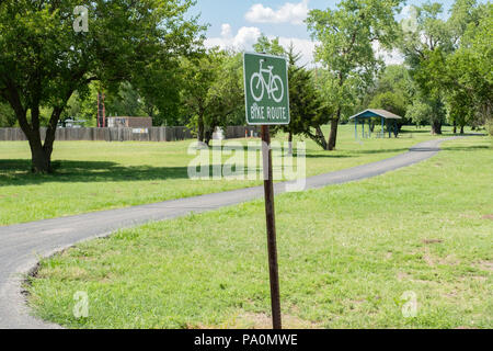 A bike route pole sign next to a bike path in a community park. USA. - Stock Image