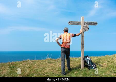 Mature male hiker on The Cleveland Way National Trail coastal footpath near Saltburn on the North Yorkshire coast. England.UK - Stock Image