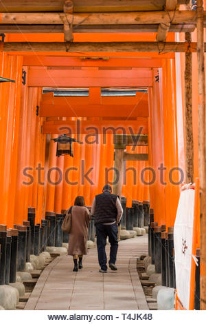 Man and woman walking beneath the Senbon Torii the highlight of the Fushimi Inari Taisha Shinto shrine, the vermilion red-orange color is associated w - Stock Image