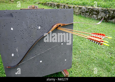 Traditional 'reflex / deflex' recurve bow hangs on arrows shot in tight group. - Stock Image
