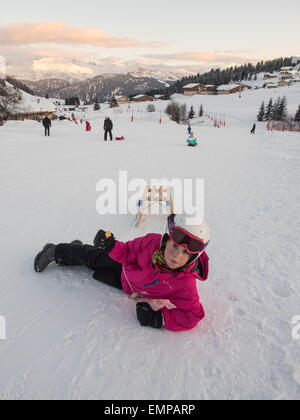 small girl in ski clothes and helmet playing on the piste with a sledge under evening light with mountain view behind - Stock Image