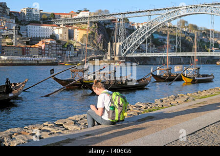 A young woman sitting waterfront riverside Cais de Gaia with a view of Dom Luis Bridge, River Douro and boats in Porto Portugal Europe  KATHY DEWITT - Stock Image