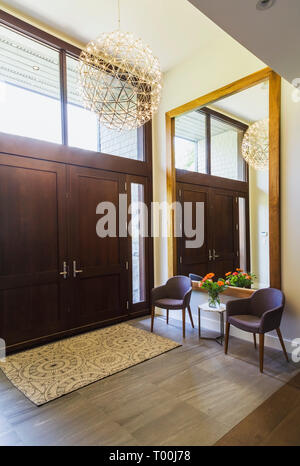 Charcoal grey upholstered chairs and small marble top table with mixed cut flowers in glass vase in front of large wood-frame mirror in house entryway - Stock Image