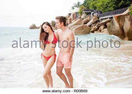 Young couple wearing swimwear walking on beach - Stock Image