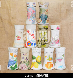 Jars decorated with decoupage technique arranged in a triangular manner. Decoupaged jars have different decorative motifs on them. - Stock Image