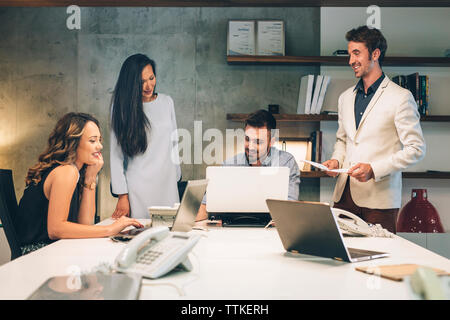 Business people discussing at desk in illuminated office - Stock Image