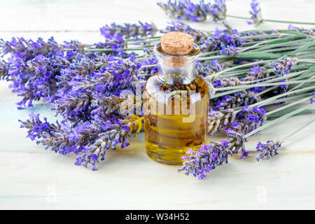 Lavender essential oil with fresh lavender flowers on a rustic wooden background with a place for text - Stock Image