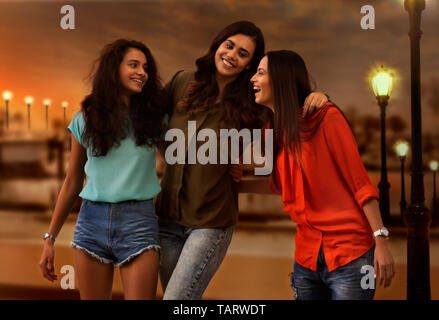 Three girl friends standing outdoors in evening and talking - Stock Image