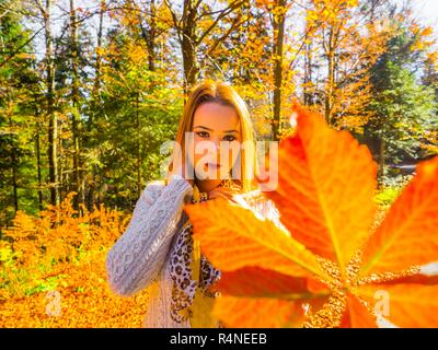 Autumn colors teen girl in woods looking at camera serious behind big leaf - Stock Image