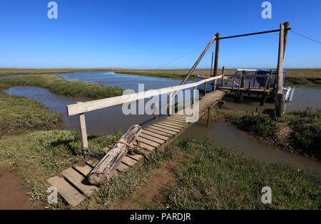 Old wooden jetty and a boat at Thornham Harbour on the North Norfolk coast. - Stock Image