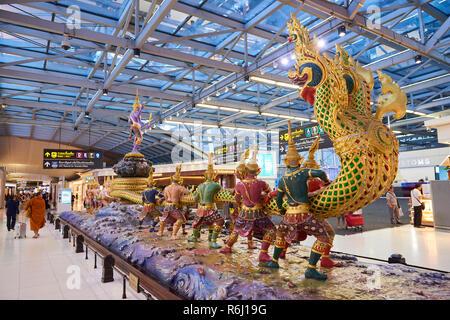Statues representing the Hindu Churning of the Milk story in Suvarnabhumi Airport lobby in Bangkok, Thailand. - Stock Image
