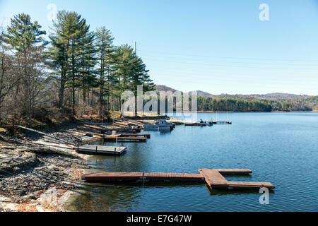 Wooden floating docks and boats along the shore of Lake Glenville near Cashiers, North Carolina on an autumn afternoon. - Stock Image