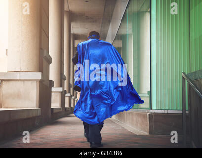 A business man is dressed as a super hero with a blue cape running in the city for a urgent job or leadership concept. - Stock Image