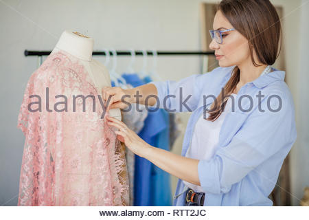 Portrait of a caucasian attractive dressmaker creating a wedding dress of a lace fabric. Exclusive tailored sewing of dress, dressed on a mannequin. S - Stock Image
