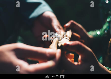 Married couple with traditional wedding dress showing their wedding rings in a dark lighting.selective focus - Stock Image