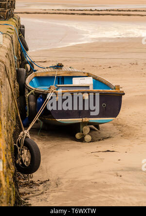 A small boat aground on the sandy beach moored to the harbour wall at low tide. - Stock Image