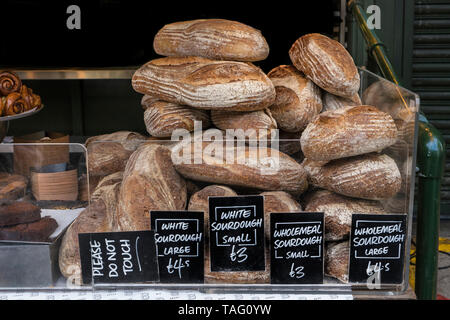 Speciality bread Borough Market Bakery 'Bread Ahead' stall with variety of attractive hand made artisan breads on display for sale with white Sourdough bread displayed in foreground. Artisan speciality bakery stall at Borough Market Southwark London UK - Stock Image