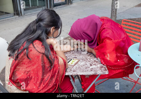 Celebrating the end of Eid, a Mulsim woman from Bangladesh gets a henna decoration on her arm & hand. At Diversity Plaza in Jackson Heights, Queens. - Stock Image
