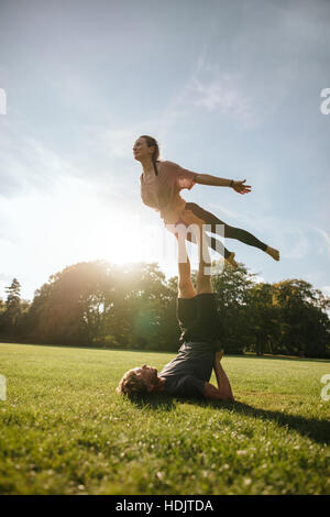 Vertical shot of fit young couple doing acrobatic yoga. Man lying on grass and balancing woman in his feet at the - Stock Image