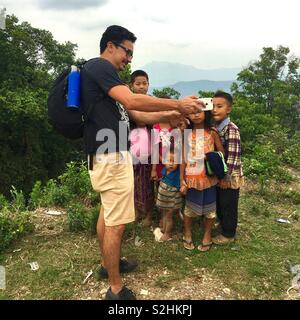 Tourist showing local children a photo of them on an iPhone in village in Laos - Stock Image