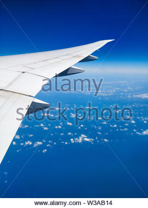 Plane wing above the clouds view clear sky - Stock Image