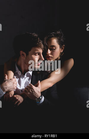 attractive brunette woman in black dress standing behind couch and hugging handsome man in suit sitting on black background - Stock Image