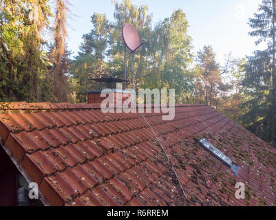 Inspection of the red tiled roof of a single-family house, inspection of the condition of the tiles on one roof side - Stock Image