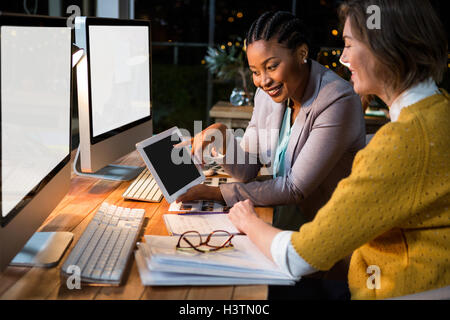 Businesswoman discussing with colleague over digital tablet - Stock Image