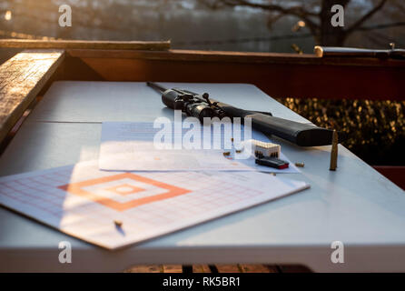 A 22-caliber rifle sits on a table with bullets around it as the sun sets. - Stock Image
