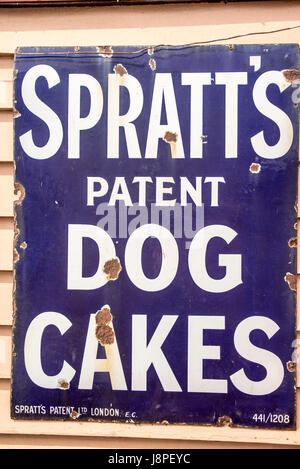 Old metal advert fro Spratt's dog cakes adorning a heriatage steam railway in UK bearing many dust spots and - Stock Image