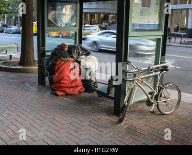 CHARLOTTE, NC, USA-10/30/18:  An apparently homeless woman, with bags of possessions, sleeps at a bus stop on Tryon St. - Stock Image
