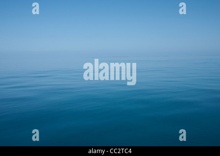 Becalmed seas on the Great Barrier Reef, Australia. The calm waters, reflecting the sky, make it hard to distinguish - Stock Image