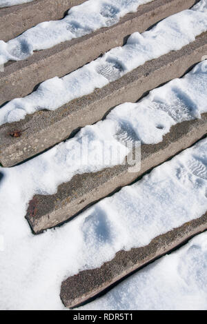 Stairs covered by snow and footprints. - Stock Image