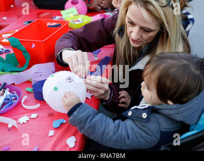 Los Angeles, USA. 17th Feb, 2019. A child makes a Chinese lantern with his mother during a celebration of Chinese Lunar New Year at the Original Farmers Market in Los Angeles, the United States, Feb. 17, 2019. The Lunar New Year celebration on Sunday attracted both locals and tourists. It kicked off with the unveiling of a steel handmade pig statue weighing 400 pounds (181 kg) in honor of this year's zodiac sign, followed by a kung-fu demonstration, acrobatic performances, a magic show and a traditional lion and dragon dance. Credit: Li Ying/Xinhua/Alamy Live News - Stock Image