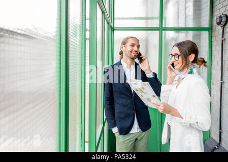 Business people talking phone standing in the beautiful green hall with glass partitions - Stock Image