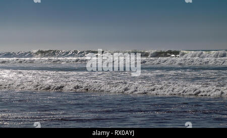 Clear blue skies and sunlight with Atlantic Ocean waves crashing onto sand beach with no people in Agadir, Morocco, Africa - Stock Image