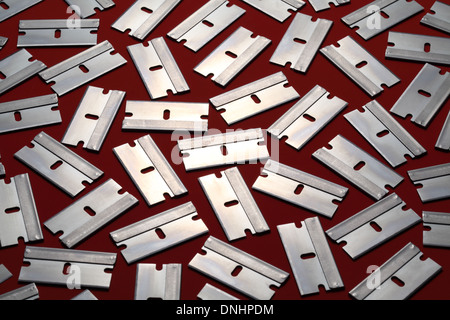 A pattern of many metal razor blades on a red background. - Stock Image