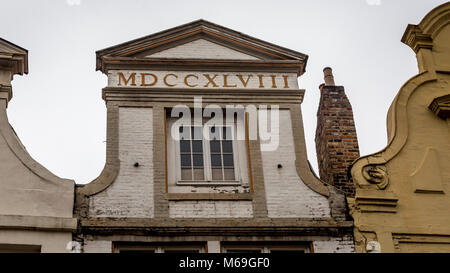 Palladian shaped roof facade with the date 1748 displayed in Roman Numerals over a square window frame in the architectural - Stock Image