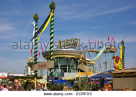 Visitors to Oktoberfest in Munich, Germany, mill around food booths and enjoy the roller coaster and other rides. - Stock Image