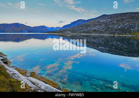 Stark mountains are reflected in the calm water of fjord Ejfjord on Ofoten in northern Norway. - Stock Image