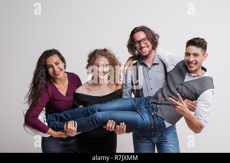 A group of young cheerful people holding a friend in a studio, enjoying a party. - Stock Image