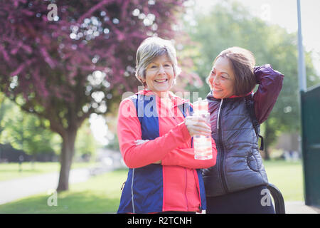 Portrait confident active senior female runner friends drinking water in park - Stock Image