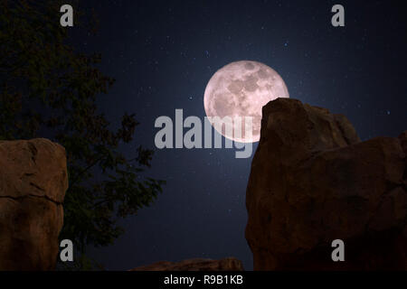 A full moon rises in the mountains of Colorado on a clear starry night. - Stock Image
